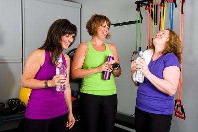 Group of 3 women relaxing after a workout in a gym
