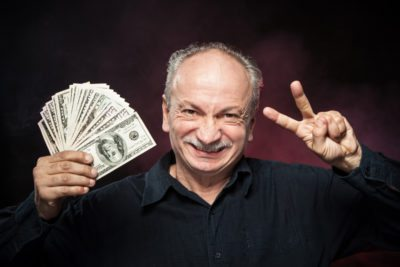 Lucky old man holding with pleasure group of dollar bills. Focus on face